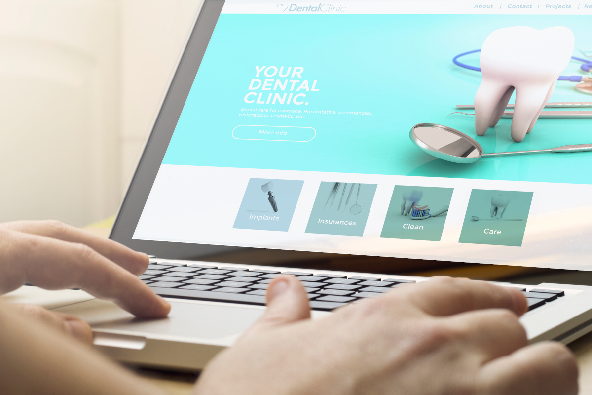 Hands typing on a laptop showing a dental website